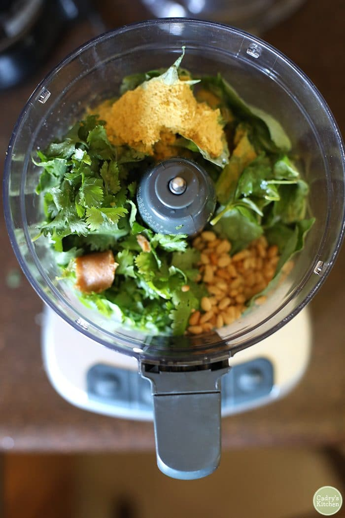 Overhead food processor with basil, nutritional yeast, cilantro, miso paste, and pine nuts.