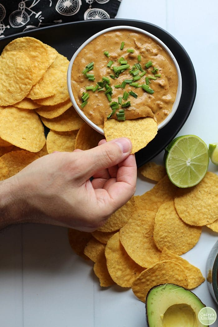 Hand dipping tortilla chip into vegan cheese dip plus tortilla chips, lime, and avocado.