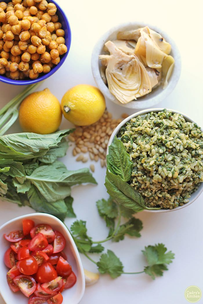 Overhead ingredients for pesto rice - lemons, roasted chickpeas, tomatoes, basil, lemons, and artichoke hearts.