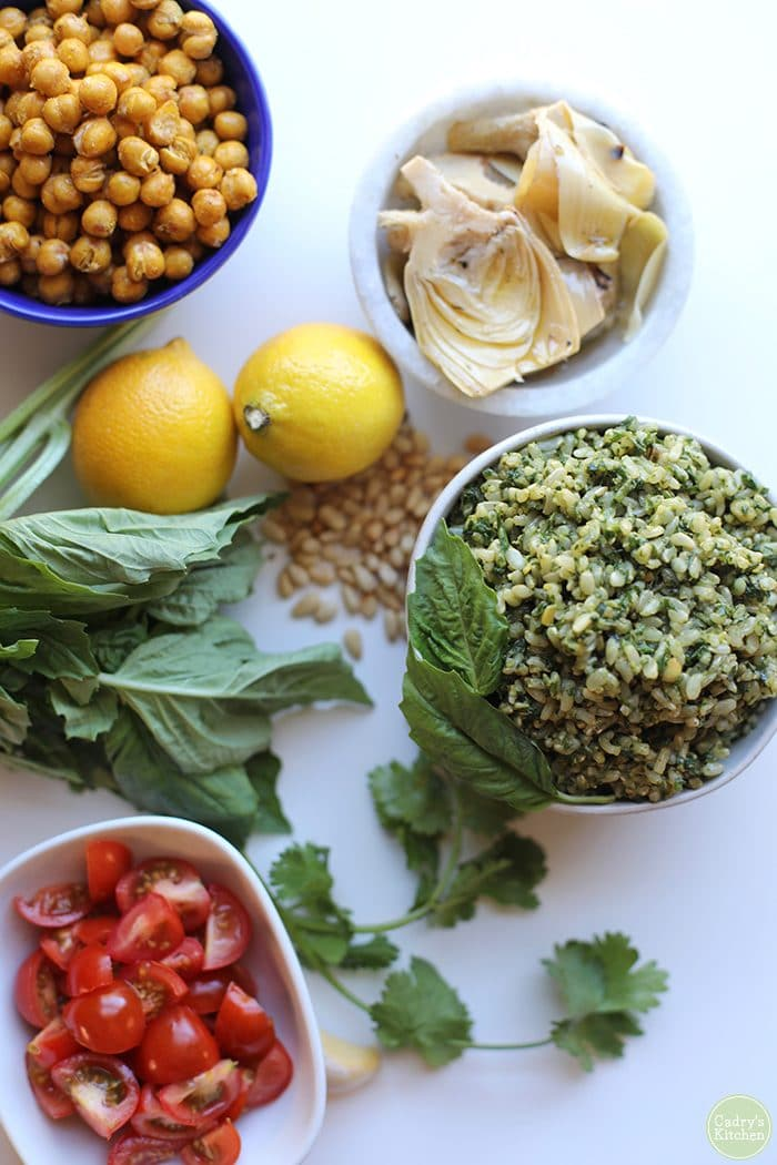 Overhead vegan pesto rice with lemons, cherry tomatoes, basil, cilantro, pine nuts, grilled artichoke hearts, and roasted chickpeas.