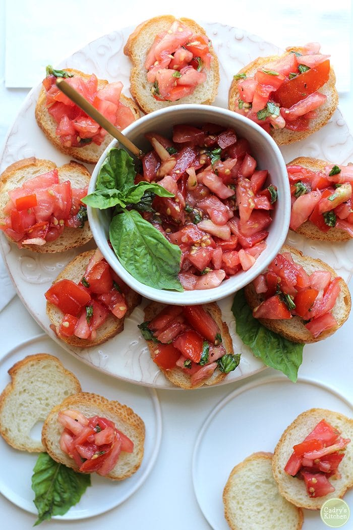 Tomato bruschetta appetizer on platter and little plates.