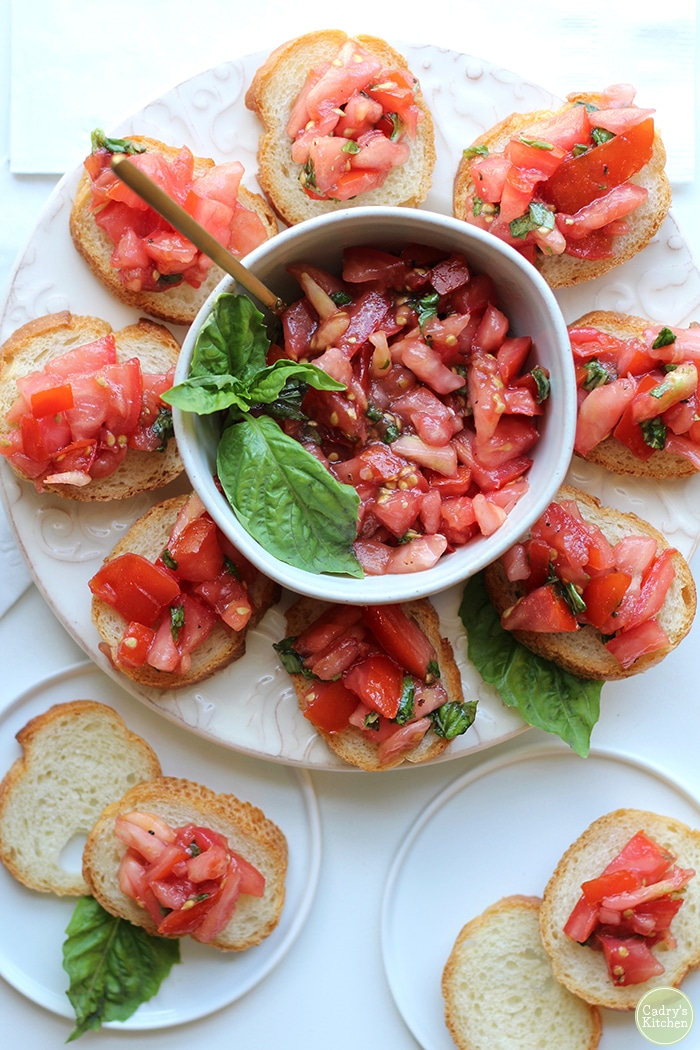 This easy tomato bruschetta appetizer offers the essence of summer. It's simply made with ripe tomatoes, fragrant basil, garlic, vinegar, oil, salt, and pepper. When the ingredients are this good, why stand in the way? Also, the crostini can be made in the air fryer,on the grill, or in the oven! #vegan #vegetarian #bruschetta #appetizer #canapes #crostini #airfryer #grill #oven