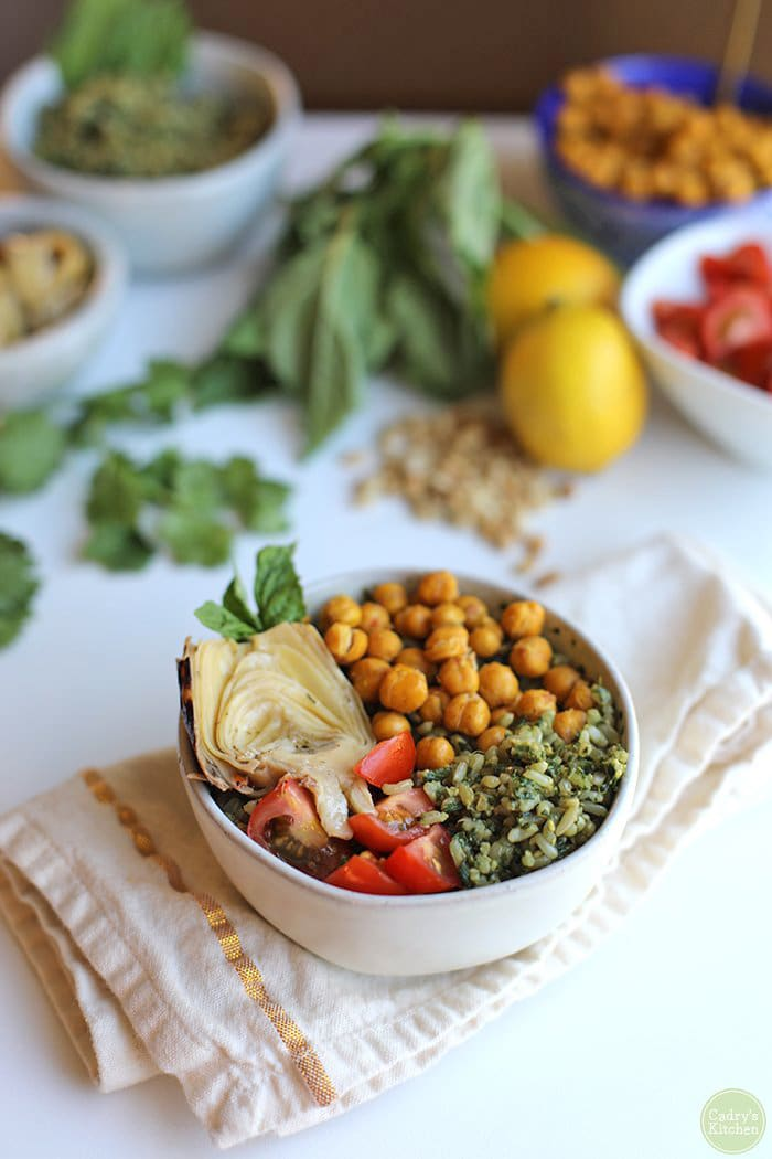 Pesto rice topped with roasted chickpeas, tomatoes, and artichoke hearts.