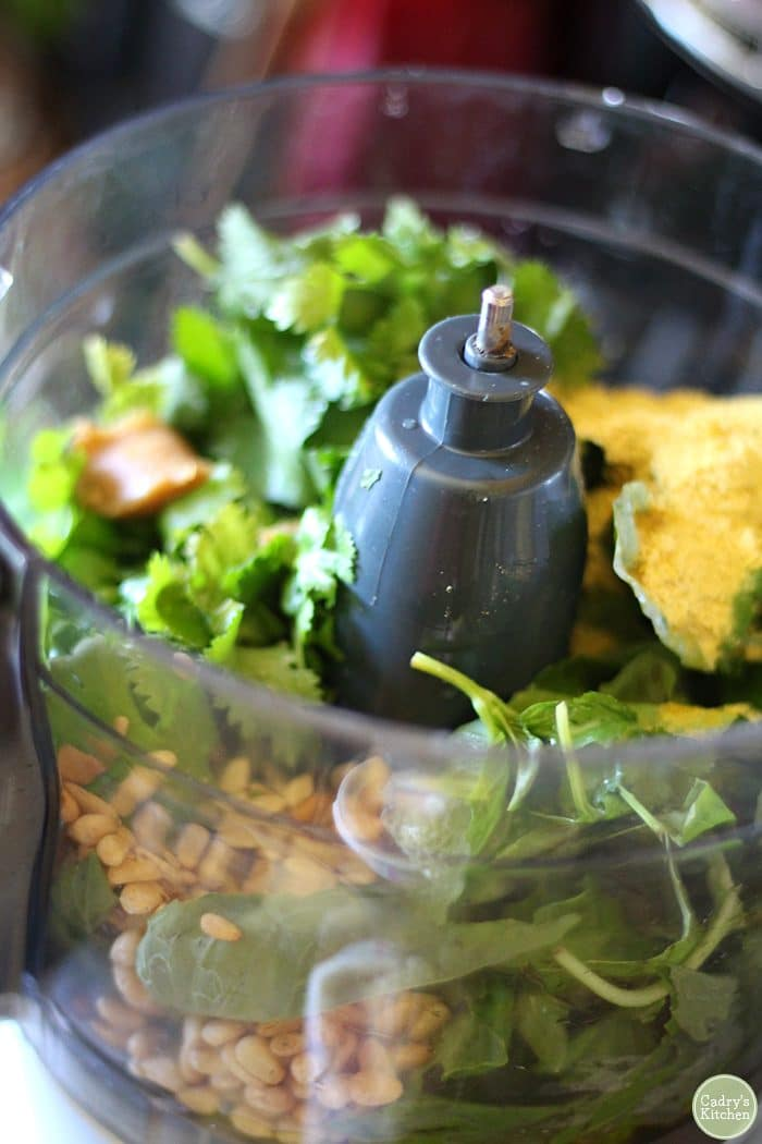 Food processor with basil, cilantro, pine nuts, and nutritional yeast flakes.