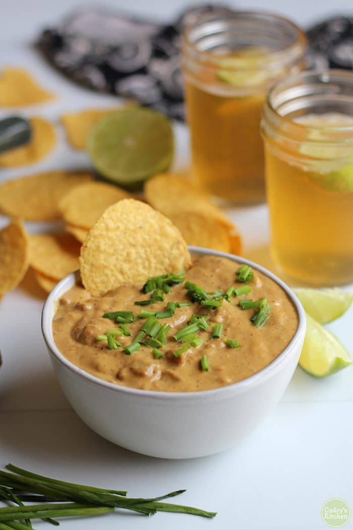 Vegan chili cheese dip in bowl with tortilla chips, Mexican beer, and limes.