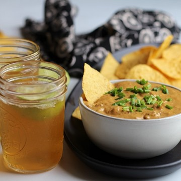 Vegan chili cheese dip in bowl, tortilla chips, and Mexican beer with lime.
