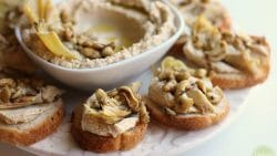 Vegan canapes with artichoke hearts & hummus on platter.