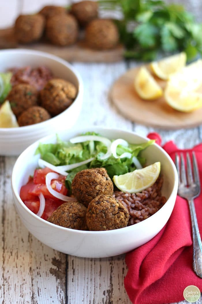 Lentil balls in bowl with lemon slice, salad, and lemon rice. Red napkin and fork on table.