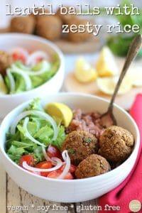 Lentil balls with zesty lemon rice in bowl alongside salad & lemon wedge.
