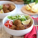 Lentil balls, lemon rice, and salad in bowls. Red napkin and fork on table.