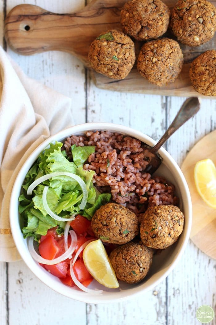 Lentil balls with lemon rice, tomatoes, green leaf lettuce, and tomatoes in bowl.