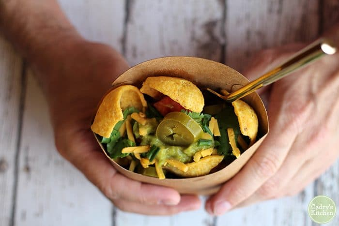 Overhead hands holding vegan walking taco with corn chips.