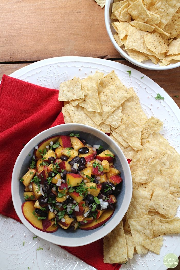 Overhead bowl of peach and black bean salsa with chips.