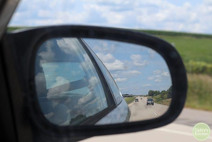 Rearview mirror on car with road & cars.