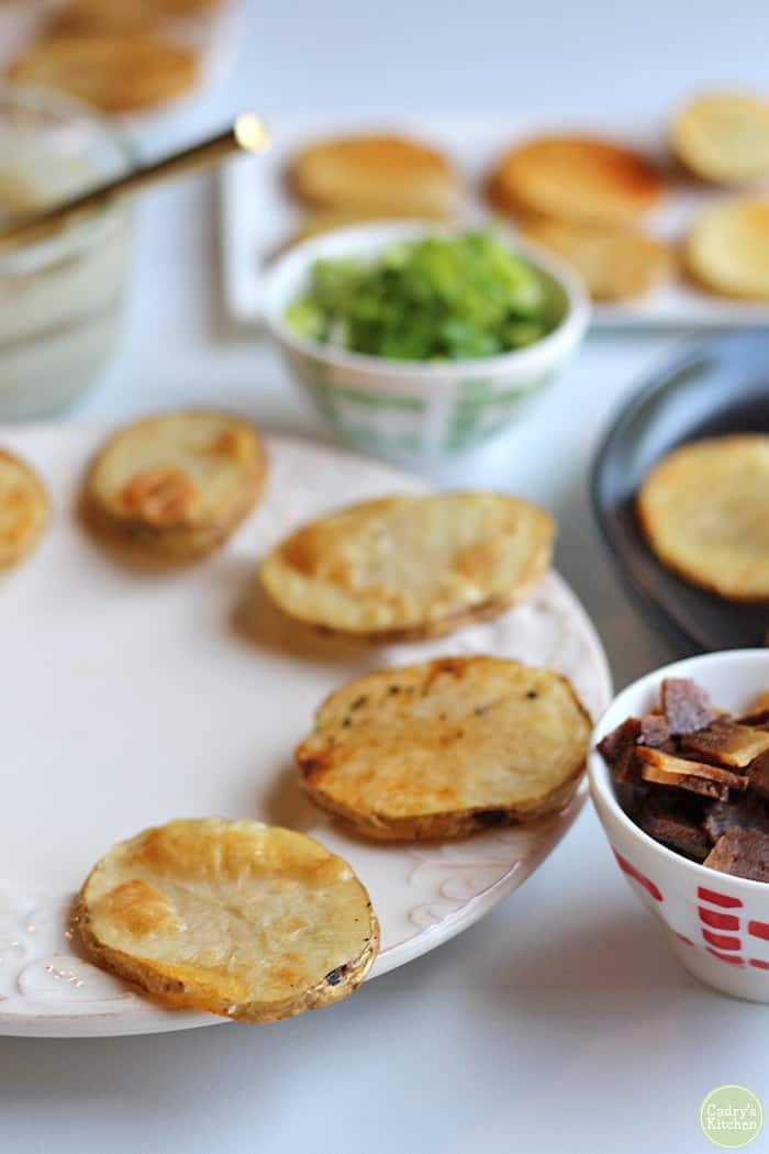 Plate with potato slices, bowls with toppings.
