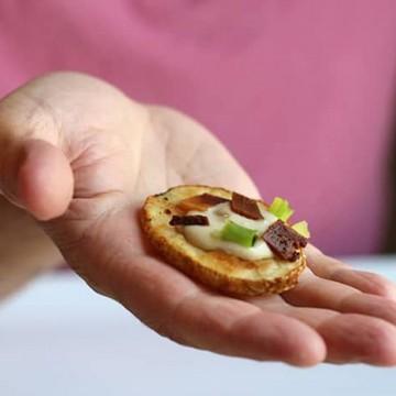 Hand holding loaded potato slice with cashew cream & seitan bacon.