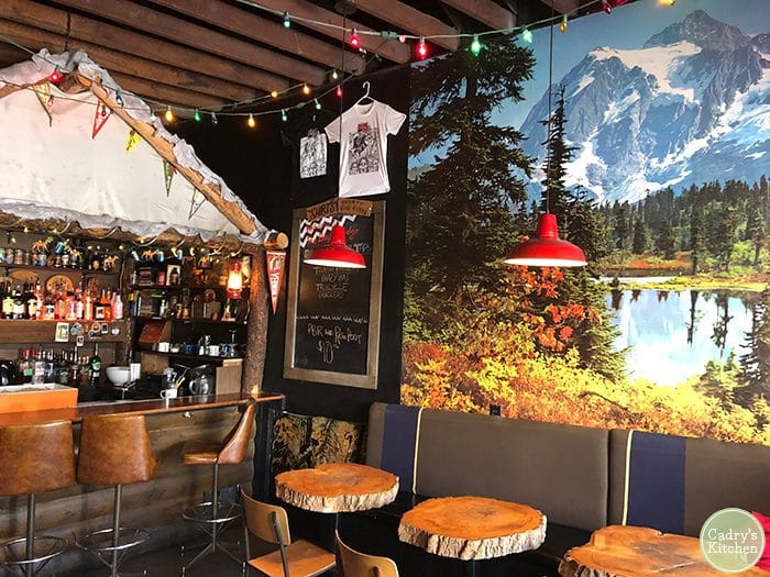 Interior Black Lodge restaurant in Vancouver with mountain mural on wall and tree tables.