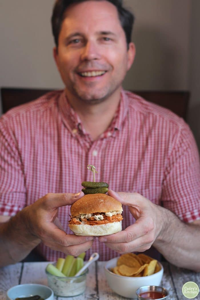 David holding Buffalo Soy Curls sandwich with pickles.