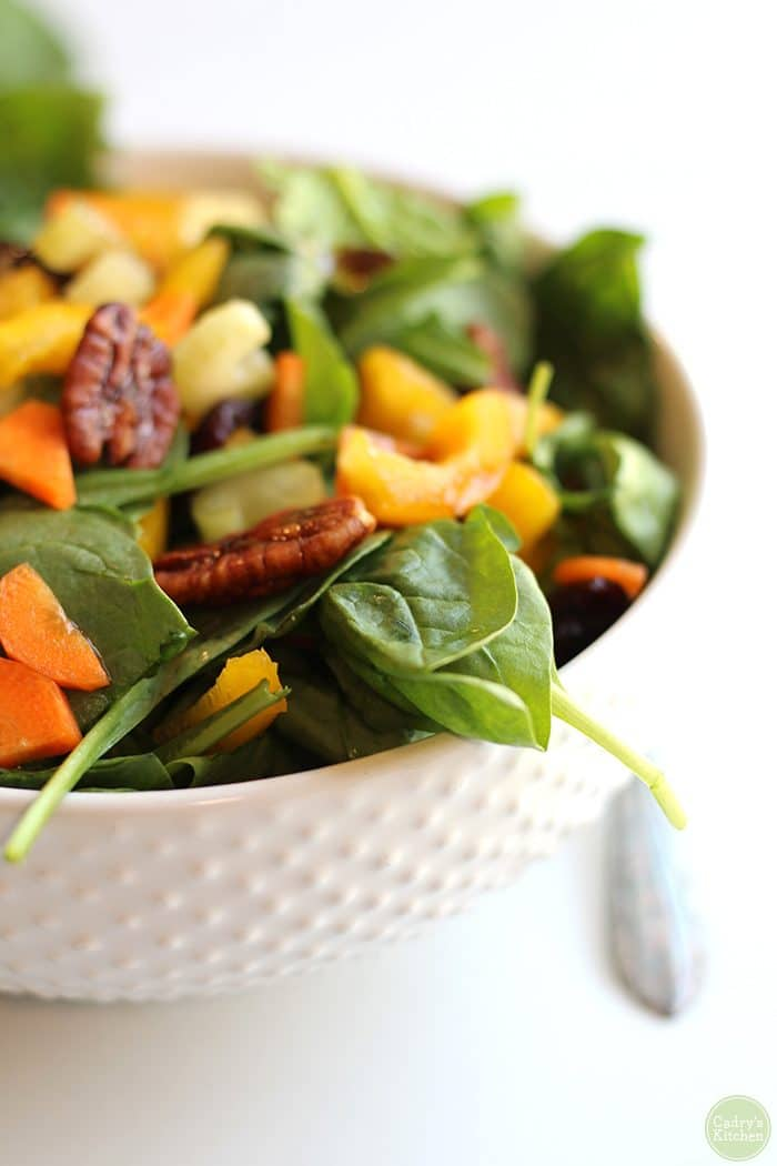 Close-up easy spinach salad with candied pecans, carrots, and bell pepper.