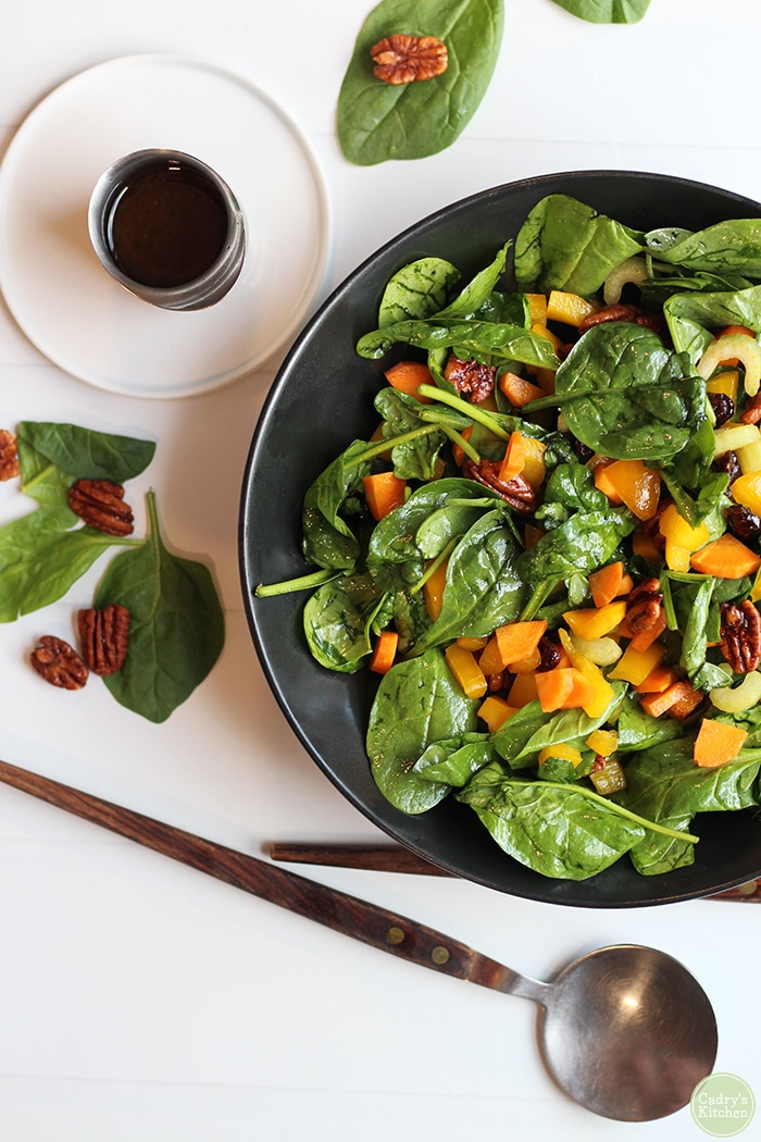 Overhead easy spinach salad with balsamic vinaigrette & spoon.