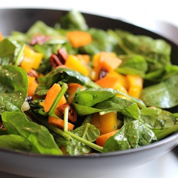 Close up easy spinach salad in black bowl.