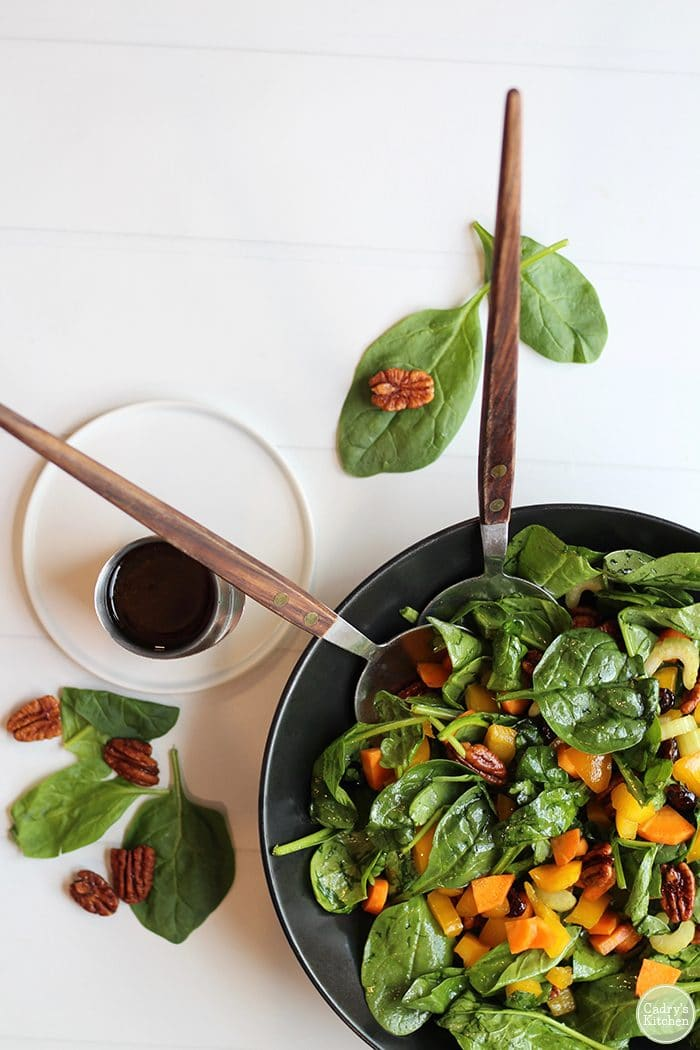 Overhead easy spinach salad with candied pecans & balsamic dressing.