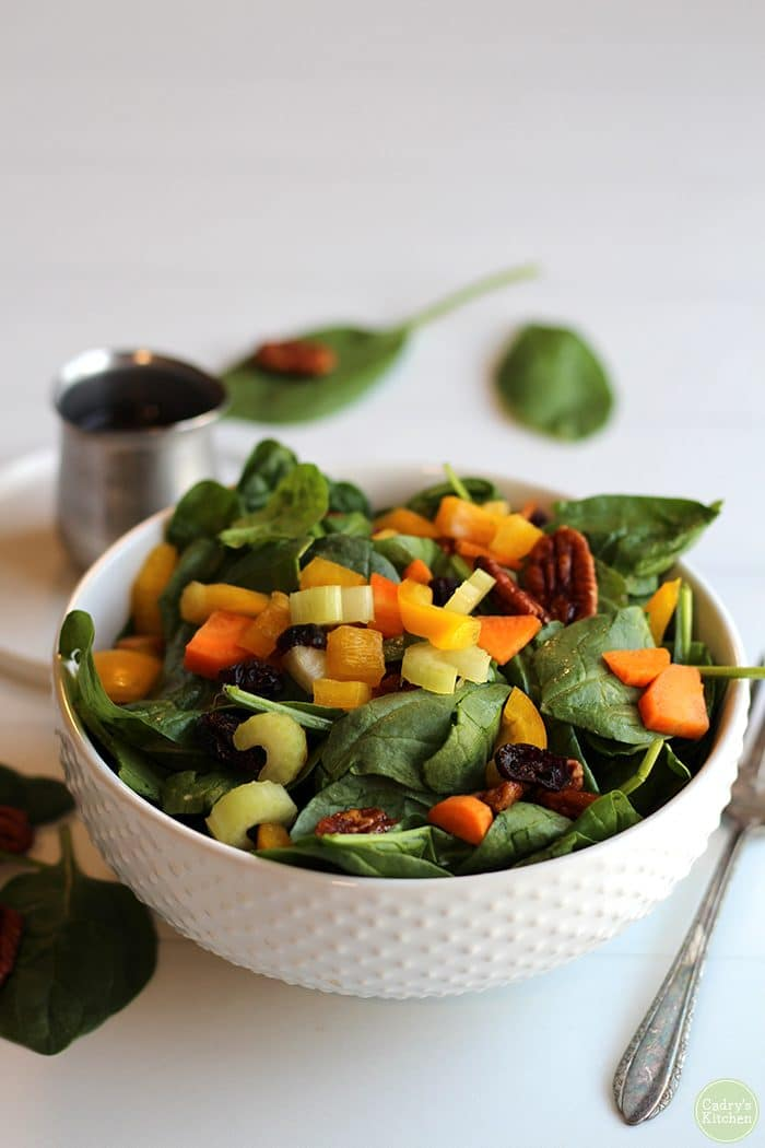 Easy spinach salad in white bowl with balsamic vinaigrette.