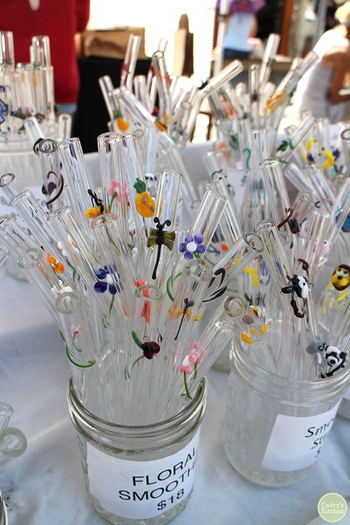 Glass straws with decorative flowers, dragonflies, and animals.