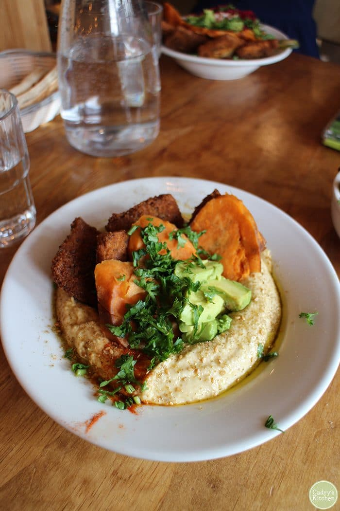 Hummus plate with smoked tofu, sweet potatoes, and avocado at Chickpea vegan restaurant Vancouver.