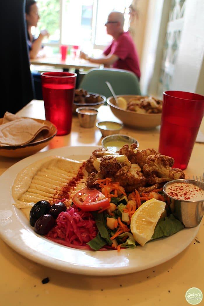 Fried cauliflower, salad, hummus, olives, and tahini on plate at Nuba.