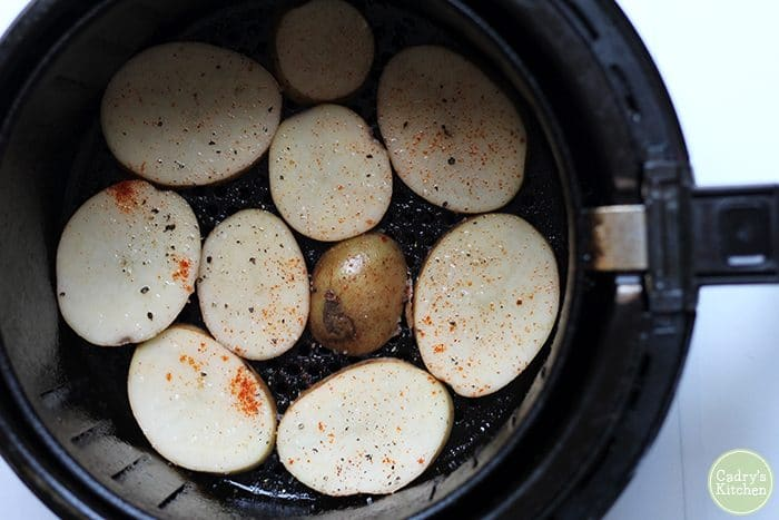Sliced potatoes in air fryer with paprika, salt, pepper, and oil.