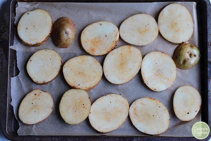 Sliced potatoes on parchment paper covered baking sheet.
