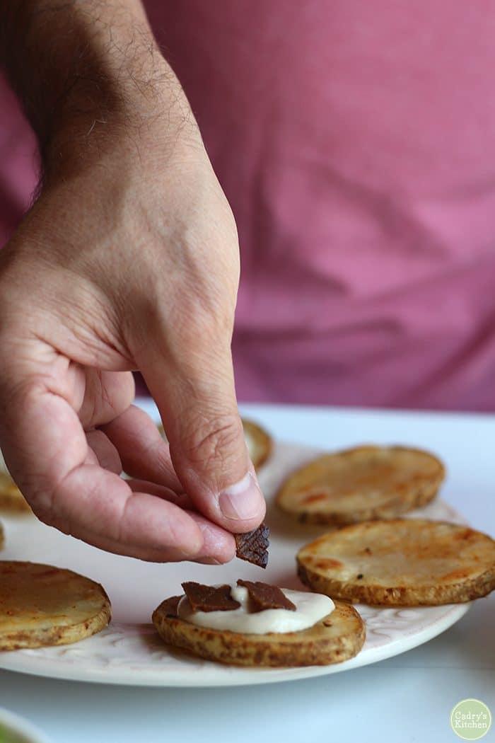 Seitan bacon on cashew cream topped roasted potato slices.