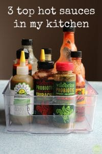 Hot sauce collection in basket + text that says 3 top hot sauces in my kitchen.
