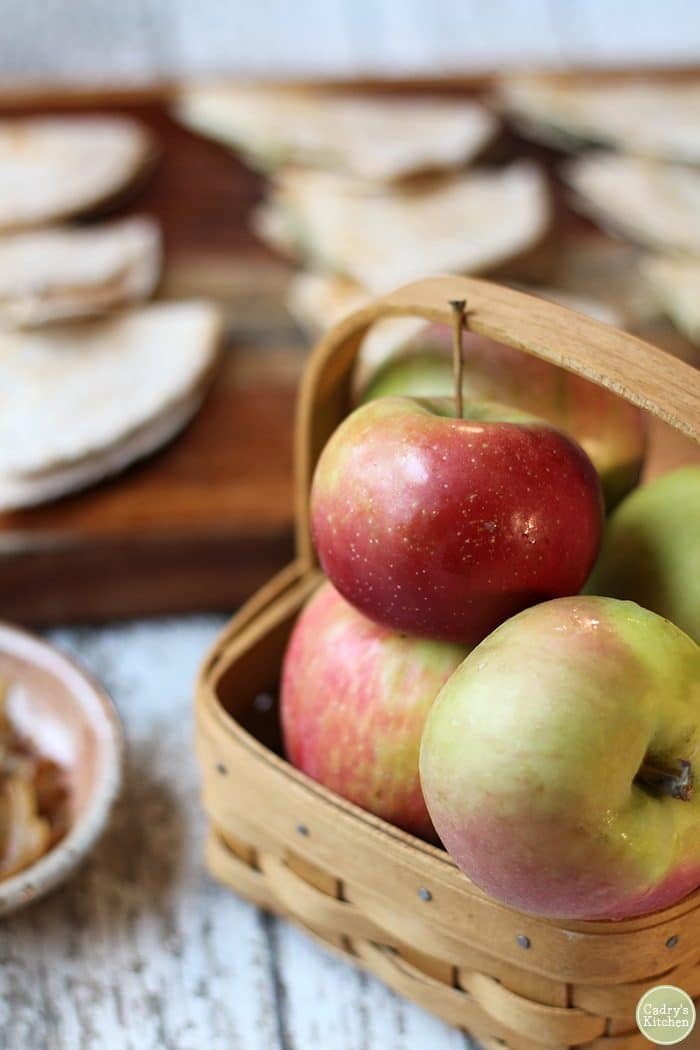 Apples in a basket with vegan quesadillas in background.
