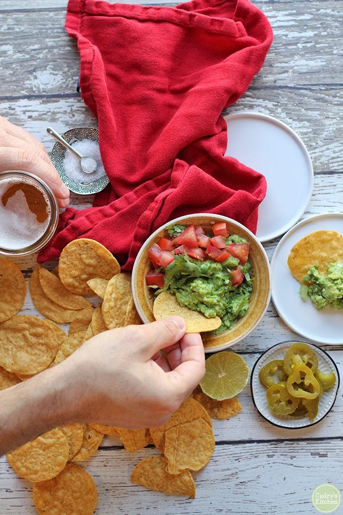 Easy guacamole recipe. Overhead hand dunking tortilla chip into bowl of guacamole. Red napkin, salt bowl, and beer on table.