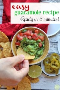 Text: Easy guacamole recipe. Ready in 5 minutes! Overhead hand dipping tortilla chip into homemade guacamole. Topped with tomatoes and cilantro.