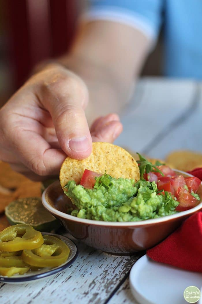 Hand dipping tortilla chip into yellow and brown bowl of easy guacamole dip.