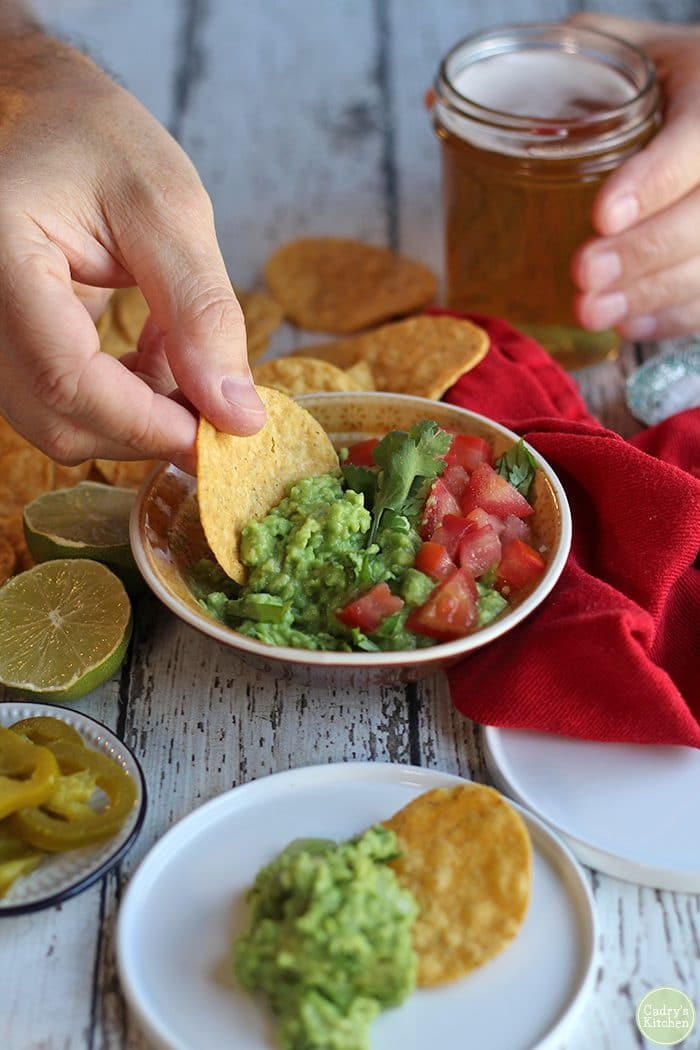 Hand dipping tortilla chip into yellow bowl of easy guacamole dip.