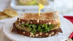 Close up vegan fried green tomato BLT on plate.