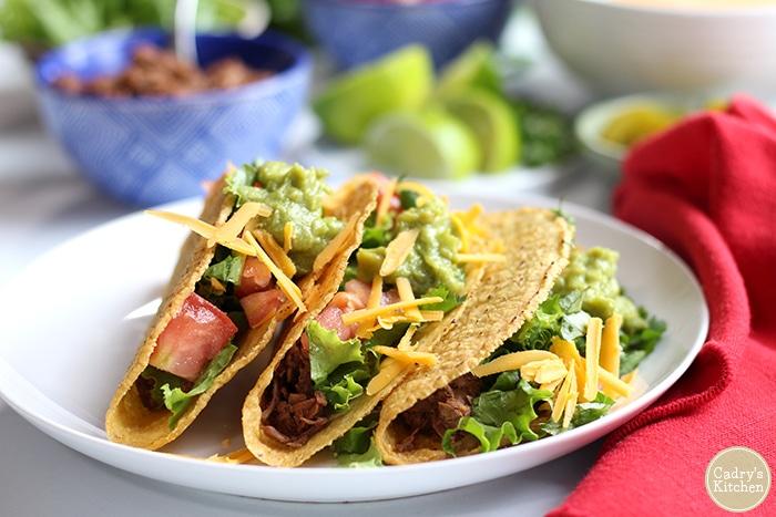 Three tacos on plate.