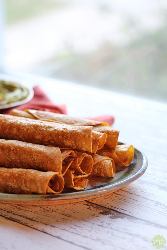 Pile of vegan taquitos on plate.