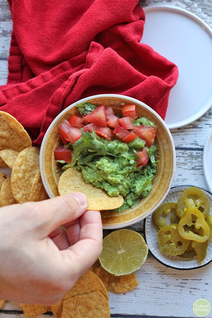 Easy guacamole recipe. Hand dipping tortilla chip into easy guacamole. Red napkin, jalapeno pepper slices, and sliced lime on table.