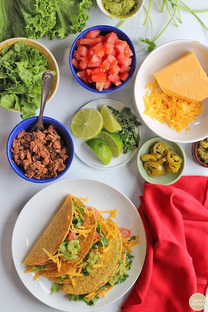 Overhead jackfruit carnitas tacos with limes, lettuce, tomatoes, non-dairy cheese, and jalapeno pepper slices.