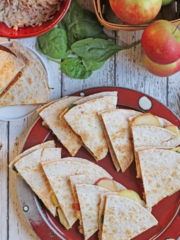 Overhead vegan quesadilla on red plate with apples, spinach, smoked mozzarella, and caramelized onions.