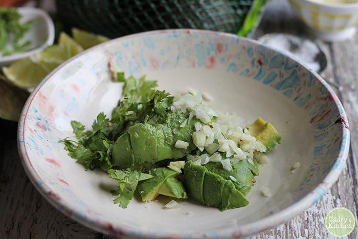 Avocado, onions, garlic, cilantro, and lime juice in a bowl. Easy guacamole recipe.