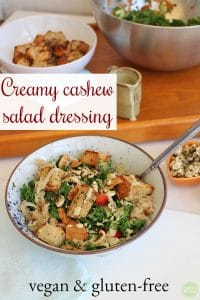 Text: Creamy cashew salad dressing. Vegan & gluten-free. Bowl of kale salad with croutons, marinated cashews, and cashew salad dressing.