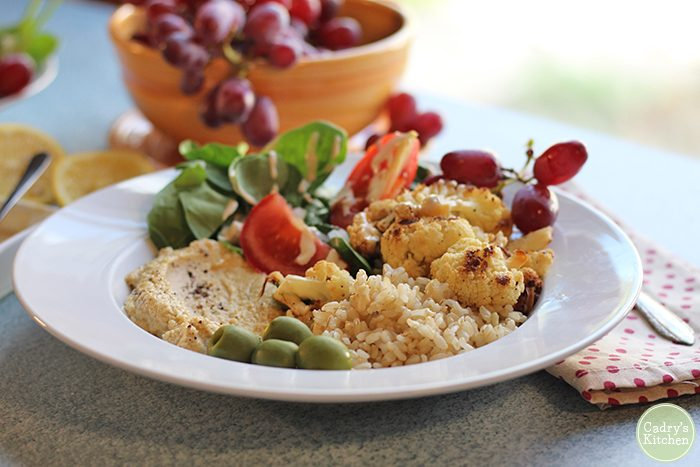 Brown rice bowl with roasted cauliflower, homemade hummus, grapes, and salad.