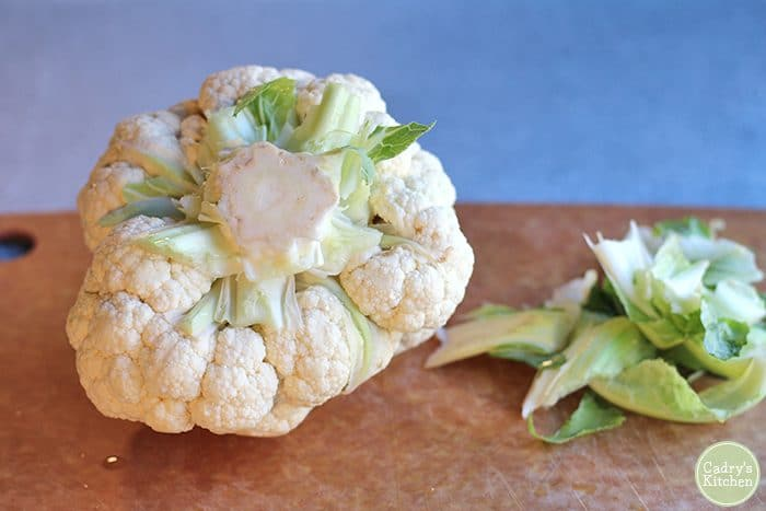 Cauliflower with stem on cutting board.