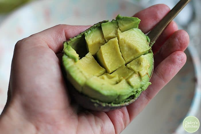 Scored avocado getting scooped out of its peel. Easy guacamole recipe instructions.